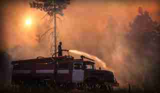 firefighter putting off fire while surrounded by a forest fire