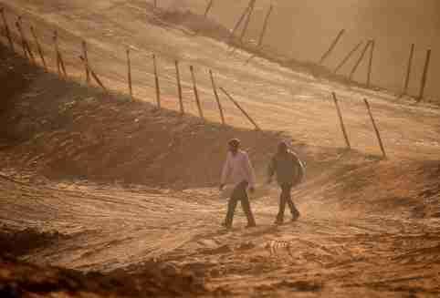 Men walk on a road under construction.