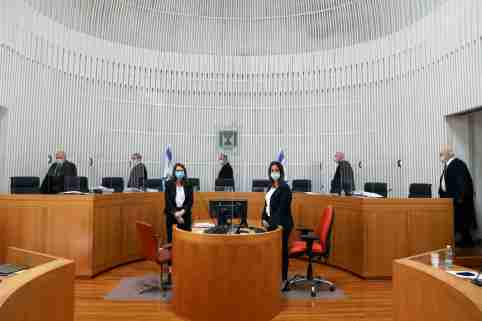 A panel of judges of the Israeli Supreme Court wear face masks as they address a discussion on a petition asking whether Israeli Prime Minister Benjamin Netanyahu can form a government legally and publicly when indictments are filed against him on a charges of fraud, bribery, and breach of trust, at the Israeli Supreme Court in Jerusalem May 4, 2020. Abir Sultan/Pool via REUTERS