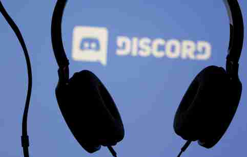 Headphones are seen in front of the logo of the Discord app logo.