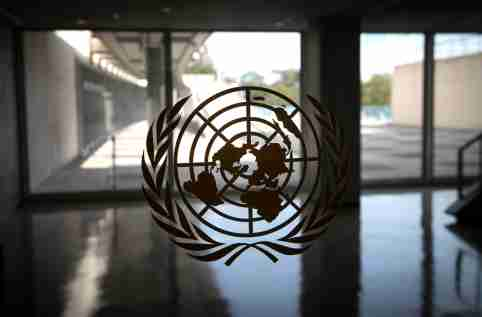 The United Nations logo is seen on a window in an empty hallway at United Nations headquarters during the 75th annual U.N. General Assembly high-level debate, which is being held mostly virtually due to the coronavirus disease (COVID-19) pandemic in New York, U.S., September 21, 2020. REUTERS/Mike Segar