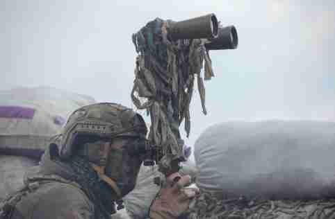 A service member of the Ukrainian armed forces uses binoculars while observing the area at fighting positions on the line of separation near the rebel-controlled city of Donetsk, Ukraine April 6, 2021. REUTERS/Serhiy Takhmazov