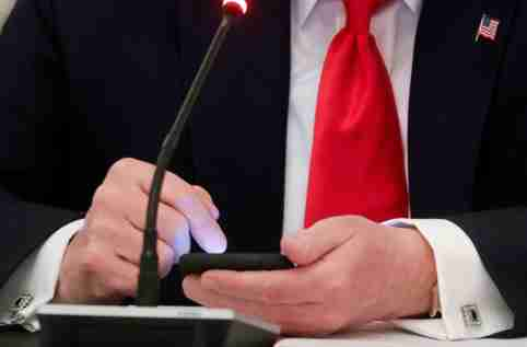 FILE PHOTO: U.S. President Donald Trump taps the screen on a mobile phone  in the State Dining Room at the White House in Washington, U.S., June 18, 2020. REUTERS/Leah Millis/File Photo