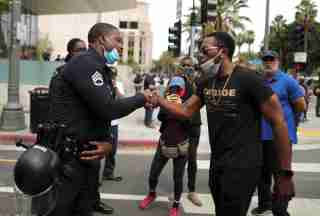A police officer shakes hands with a demonstrator during a protest against the death in Minneapolis police custody of George Floyd, outside LAPD headquarters in Los Angeles, California, U.S. June 2, 2020. REUTERS/Lucy Nicholson
