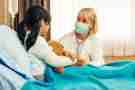 Young person with teddy bear in hospital bed speaking with a doctor in a surgical mask.