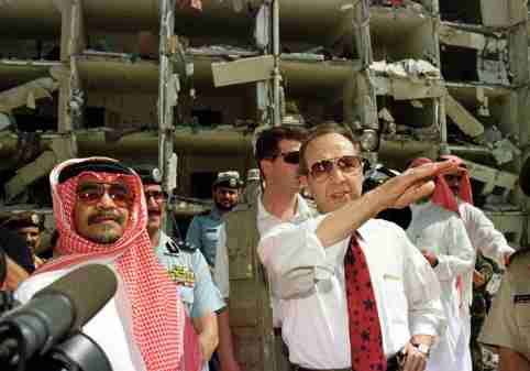 US Secretary of Defence William Perry (R), accompanied by the Saudi Ambassador to the US., Prince Bandar bin Sultan bin Abd al-Aziz Al Saud (L), survey the bomb site outside the heavily damaged apartment at the Khobar Towers housing complex for U.S. military personnel in Dhahran June 29. Nineteen American servicemen were killed, and several hundred others were injured when a bomb exploded outside the bulding on June 25.