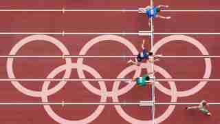 Tokyo 2020 Olympics - Athletics - Men's 400m Hurdles - Round 1 - OLS - Olympic Stadium, Tokyo, Japan - July 30, 2021. Athletes compete as Olympic rings are seen REUTERS/Peter Jebautzke