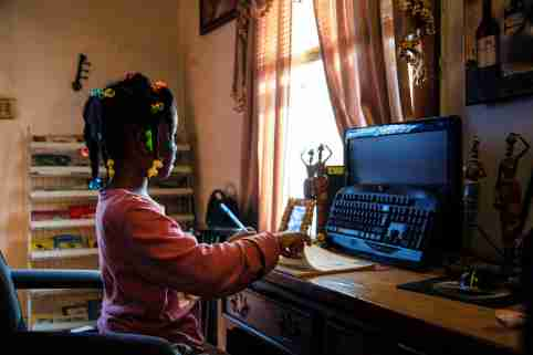 Child looks at turned off computer monitor during remote school
