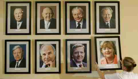 Restaurant manager Angelika Meixner places a portrait of new German Chancellor Angela Merkel beside pictures of her predecessors on a wall at the restaurant 'Kanzlereck' ('Chancellors Corner') in Berlin's government district, November 23, 2005. The pictures show (top row from L) Konrad Adenauer (German Chancellor from 1949 to 1963), Ludwig Erhardt (1963-1966), Kurt Georg Kiesinger (1966-1969), Willy Brandt (1969-1974) (lower from L) Helmut Schmidt (1974-1982), Helmut Kohl (1982-1998), Gerhard Schroeder (1998-2005) and Merkel (2005-).