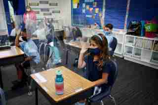 A student wearing a protective mask, attends class on the first day of school, amid the coronavirus disease (COVID-19) pandemic, at St. Lawrence Catholic School in North Miami Beach, Florida, U.S. August 18, 2021. REUTERS/Marco Bello