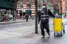An essential delivery worker wearing personal protective equipment in Tribeca, New York during the COVID-19 pandemic.