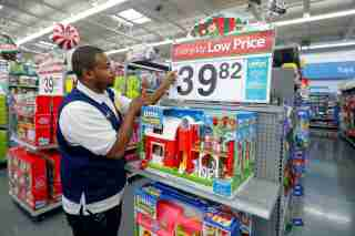FILE PHOTO: An employee puts up a price tag ahead of Black Friday at a Walmart store in Chicago, Illinois, U.S. November 23, 2016. REUTERS/Kamil Krzaczynski/File Photo