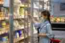 Young girl with surgical mask in freezer section of grocery store.