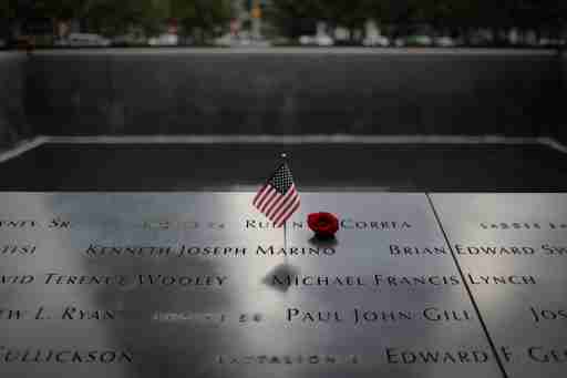An American flag and red rose stand in the names of those lost at the edge of the south reflecting pool of the 9/11 Memorial & Museum ahead of the 20th anniversary of the 9/11 attacks in lower Manhattan in New York City, New York, U.S., September 8, 2021. REUTERS/Mike Segar