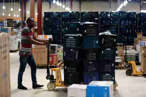 A staff member of on-line retailer Jumia, pushes a cart loaded with goods at the company's warehouse in Lagos April 10, 2014. There are two main reasons people shop online: it's cheaper or they can't be bothered with a trip to the store. And in Lagos, a city of 21 million people, a trip to the store can kill your entire day if you lose the traffic lottery. Jumia has 100,000 Nigerian customer accounts and sales are increasing by 15 percent a month.     REUTERS/Akintunde Akinleye   (NIGERIA - Tags: BUSINESS)