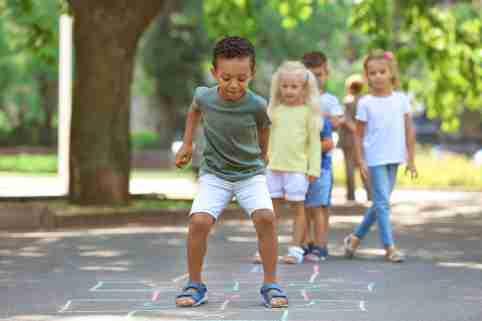 Children playing hopscotch in the park.