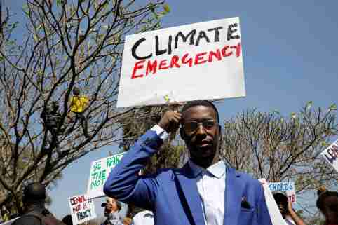 An environmental activist holds a sign as he takes part in the Climate strike protest calling for action on climate change, in Nairobi, Kenya, September 20, 2019. REUTERS/Baz Ratner