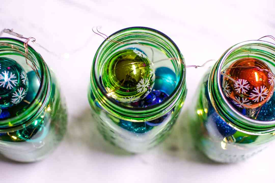 Make Mason Jar Christmas Lights and Ornament Display with simple steps and items. A DIY Christmas Mason Jar perfect for the table or shelf.