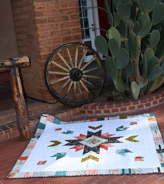 A quilt on the floor with wheel and cactus