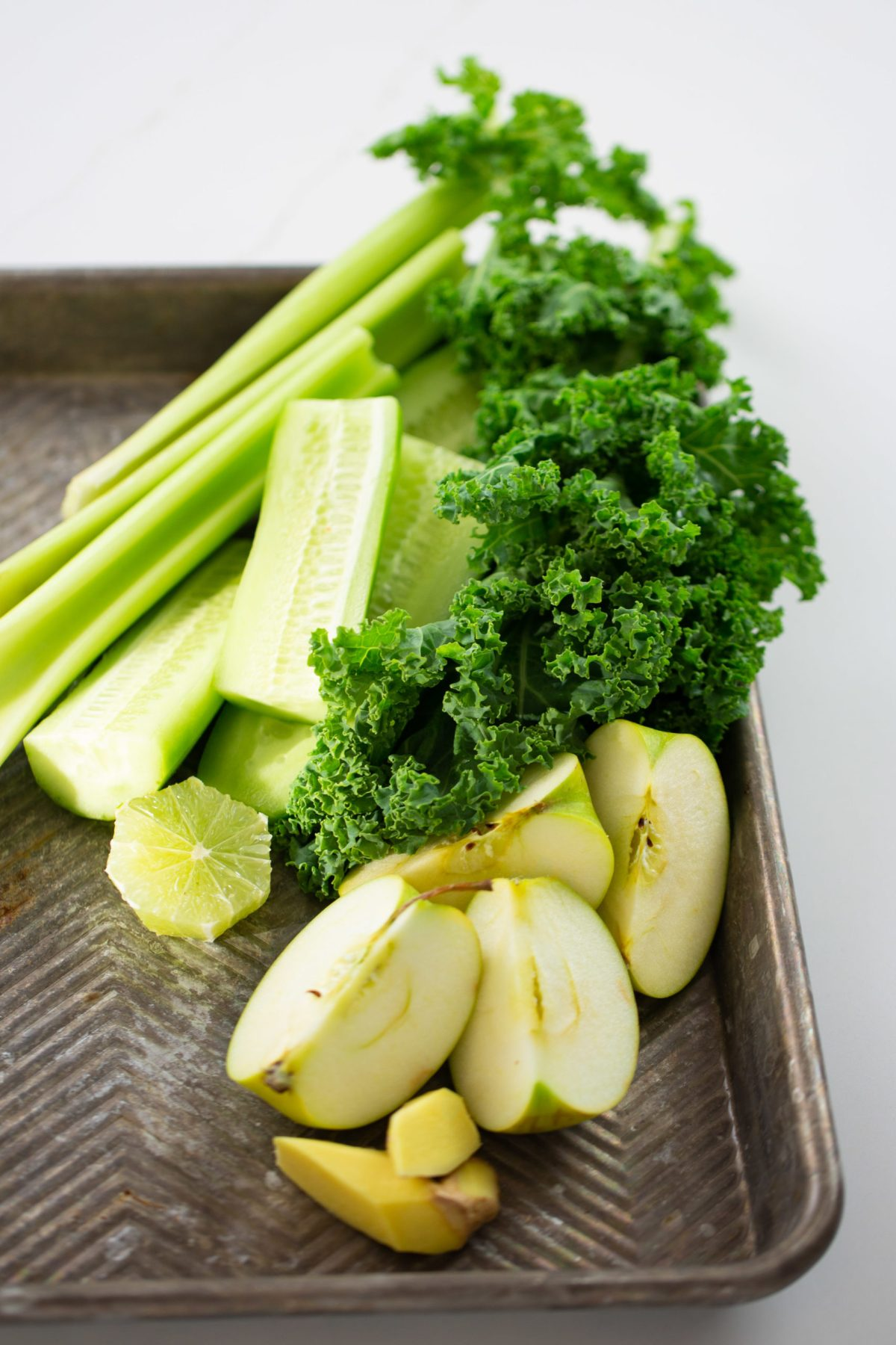 ingredients to make green juice on a tray
