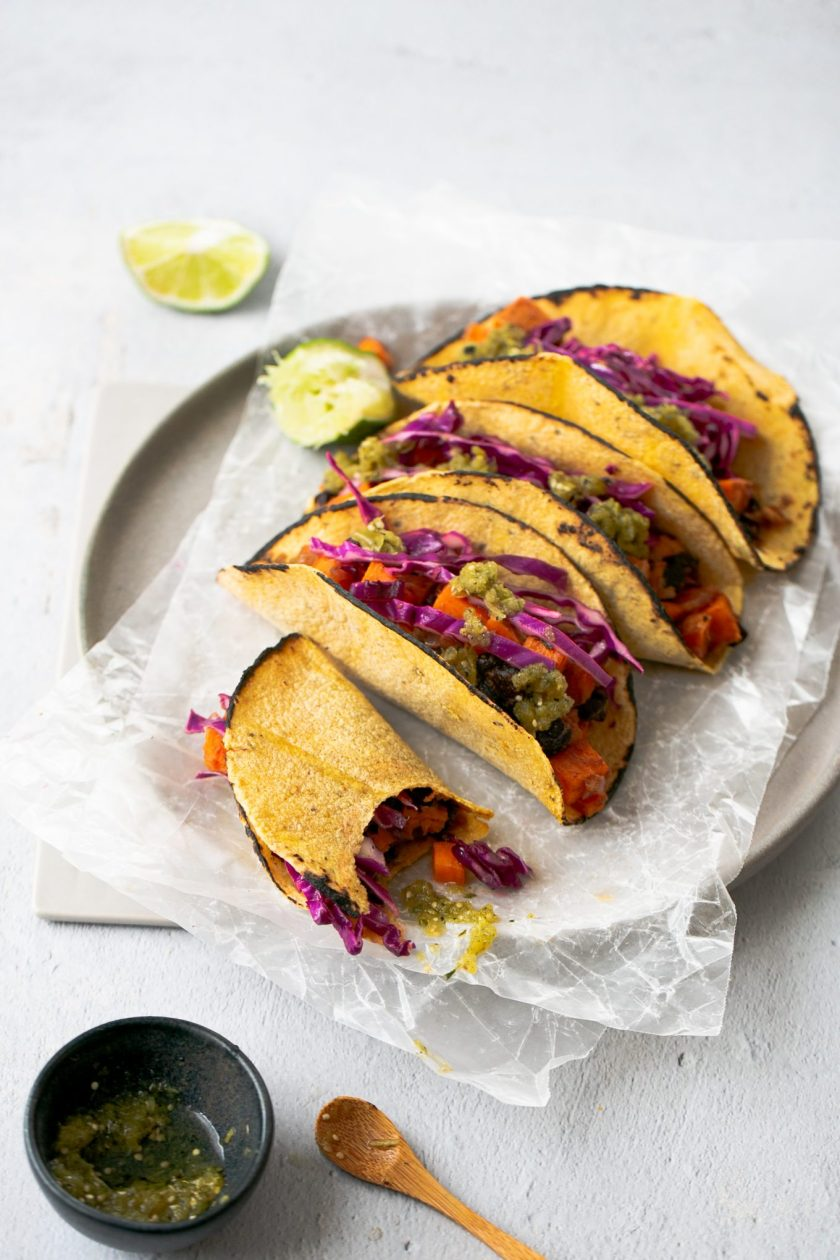 Vegan tacos with black beans and sweet potatoes topped with red cabbage and salsa verde