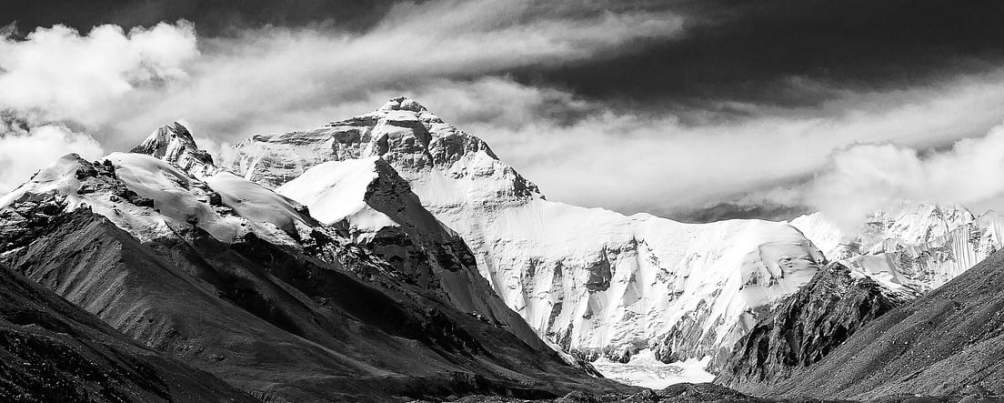A  black and whiteview of Mount Everest from Tibet, lowlands in front, clouds streaming overhead