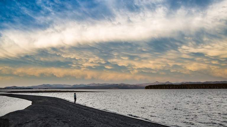 Person on a spit of land looking out over water. Overhead colourful clouds are forming