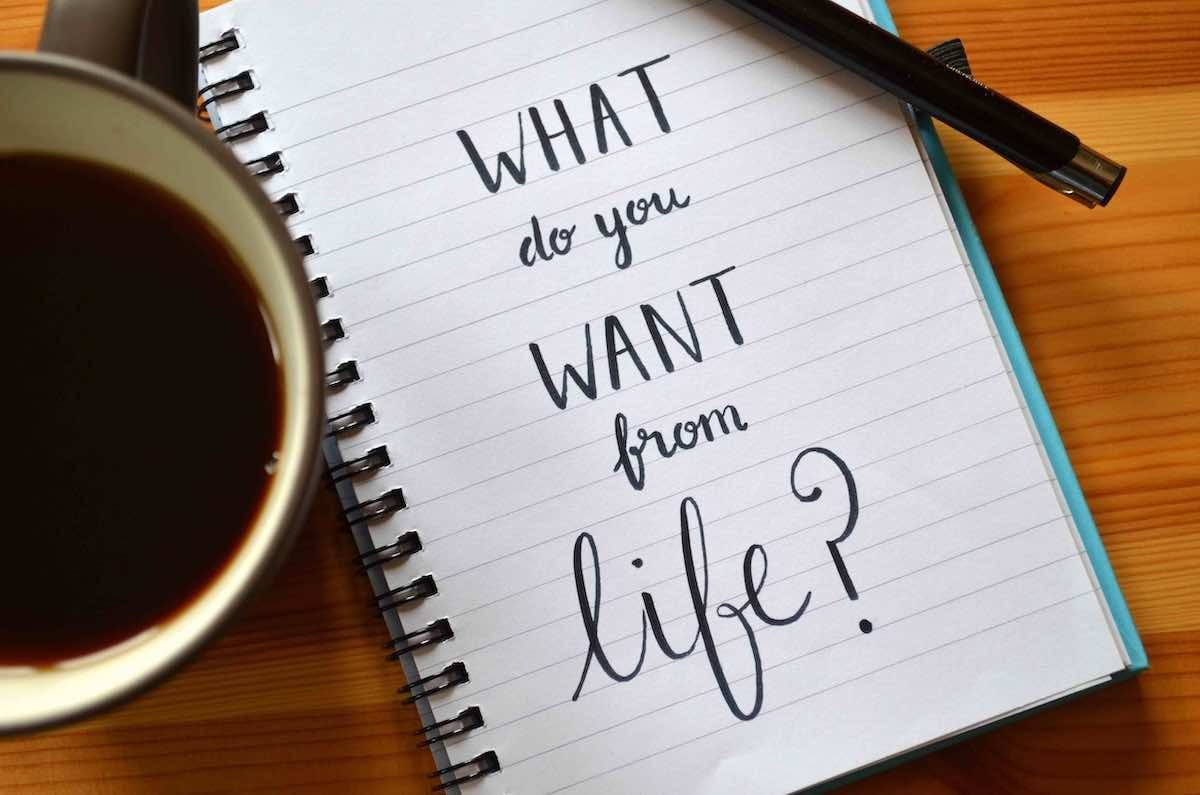"""A lined, spiral-bound notebook sits open on a wooden table between a cup of black coffee and a pen. The notebook is lined and in large letters the words """"What do you want from life"""" cover most of the page."""