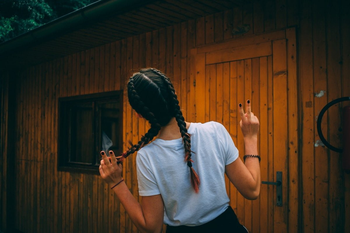 Close up of a woman with double-braided hair, with her arms and two fingers raised in celebration, as she approaches her new wood sided cottage.