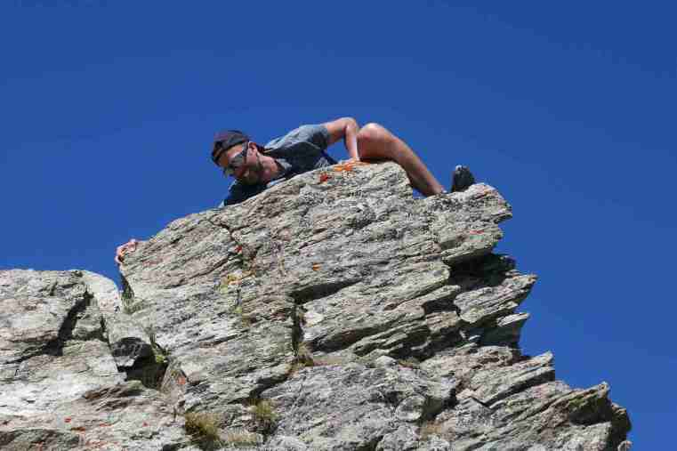 Happy climber in shorts and sunglasses summiting a grey rock outcrop. Stunningly blue sky behind.