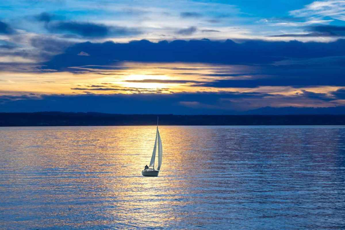 "Sail boat with sails up, silhouetted  against an orangey-gold strip of sunshine reflected off bands of dark-grey purplish clouds. Evokes a feeling of ""heading out."""