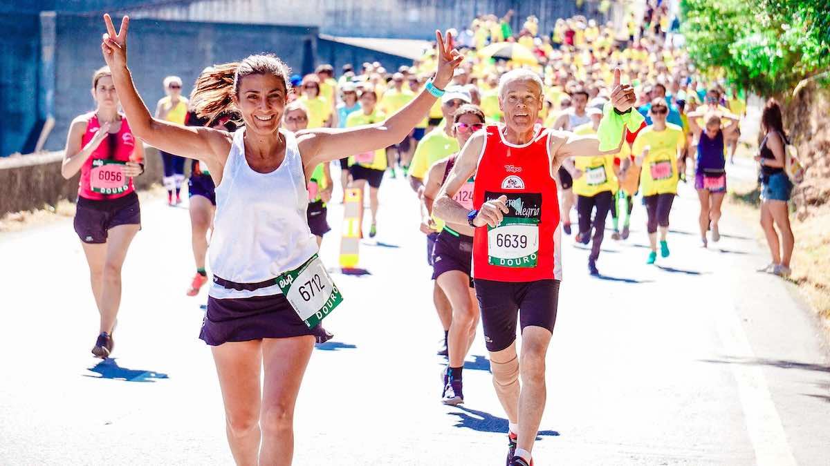 Woman in black short and white tank top raises her arms in celebration at the beginning of a marathon. Behind her, a balding man in a red tank top and black bicycling short raises one arm in a thumbs up gesture.