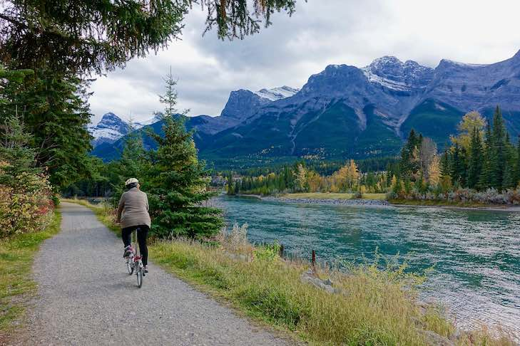 A woman cycles along a gravel path in the Canadian Rockies. On her left are spruce trees and bushes. On her right, a wide flowing river. In the background, mountain peaks poke into a cloudy sky.