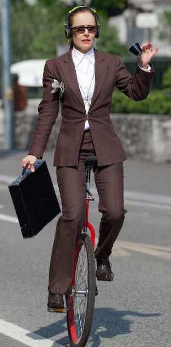 Woman in tailored grey suit and white blouse riding a unicycle with a small teacup in one hand, a brief case in the other, and headphones on her head.
