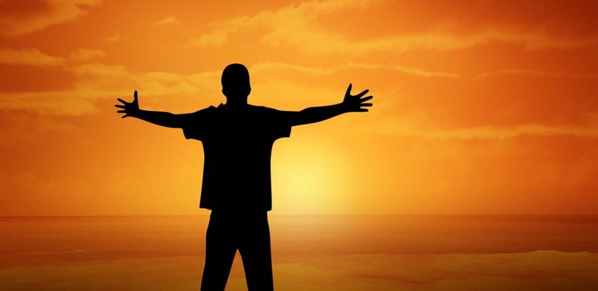 A man with arms outspread celebrating his flourishing life agains the backdrop of an orange sunset