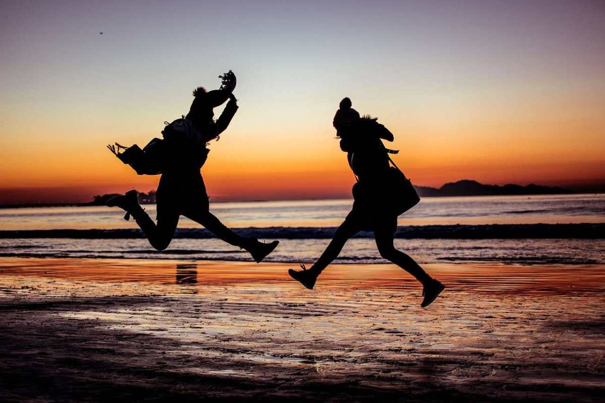 Two people jumping for joy on oceanside tidal flats at sunset. Mountains in the background. Expressing positive emotions.