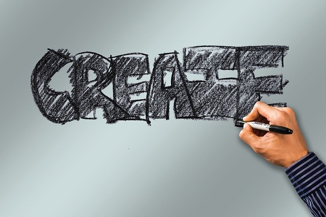 Graphic with the word CREATE in Sharpie-hatched, bold letters. A hand is holding the pen.