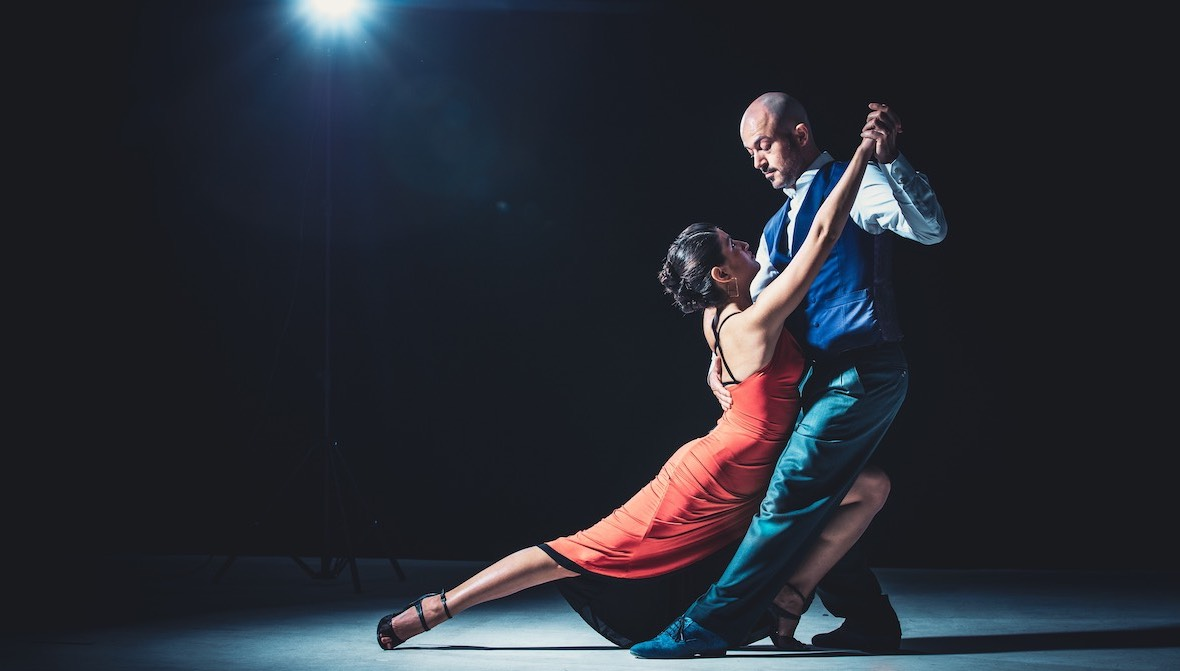 Two expert tango dancers backlit on a stage demonstrate the simplicity on the other side of complexity