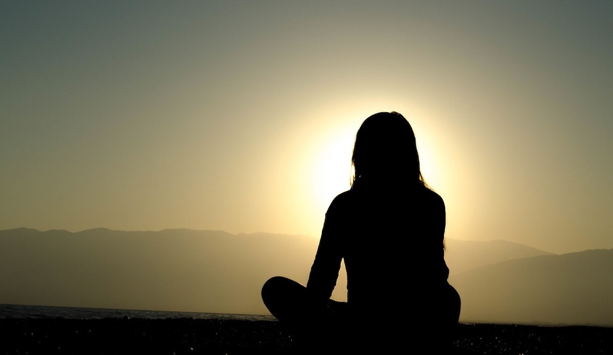 A woman sits, pondering what matters, in shadow gazing across a valley to a ridge on the other side. She is silhouetted in front of the setting sun, and seems to be embraced in a bright white and yellow aura.