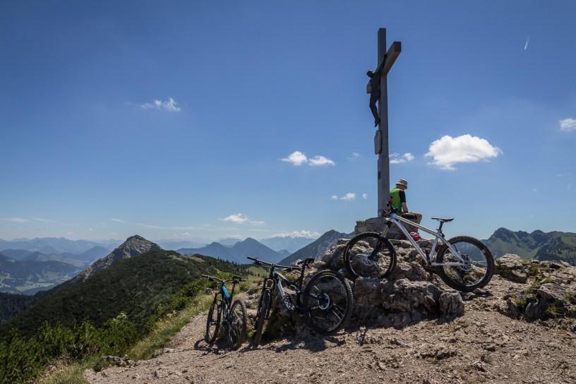 Drei Bikes warten am Gipfelkreuz auf die Abfahrt...