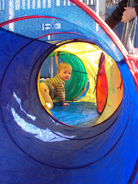 Toddlers group using outside play area with play tunnel.