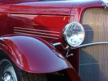 the bonnet of a shiny red classic ford; can you guess the model?