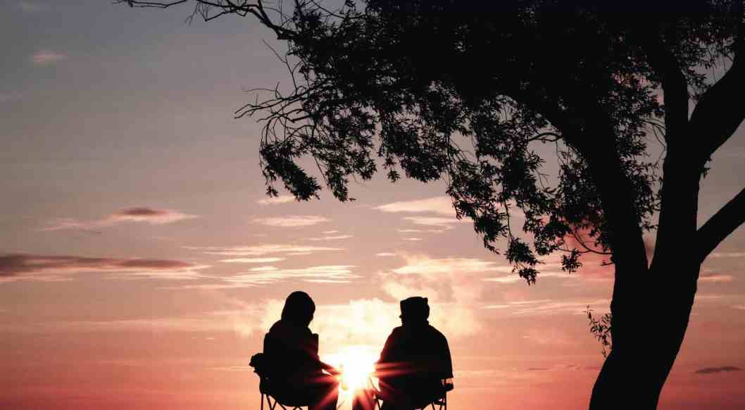 friendship two people sitting in chairs at sunset