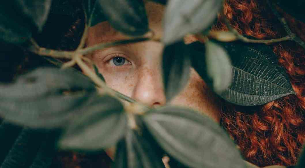 man hiding behind leaves