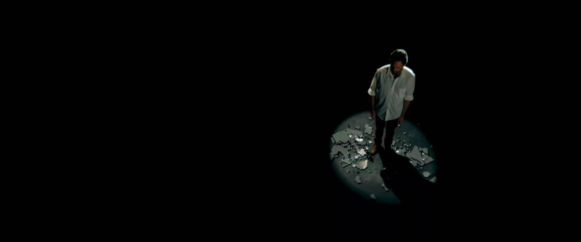 frame grab of a man under a spotlight standing on pieces of a broken mirror
