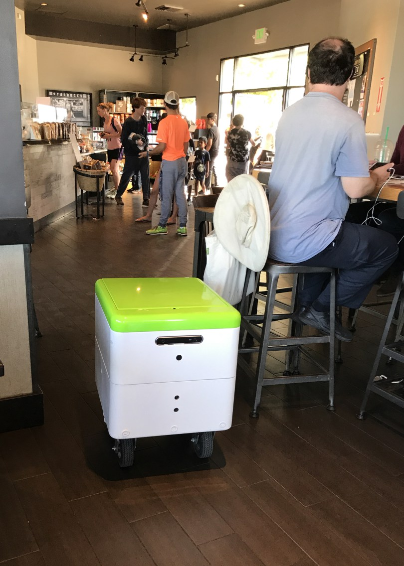 """A Robby Technologies prototype delivery robot navigates through a Starbucks in Palo Alto on Monday, Aug. 28, 2017. If it senses someone in front of it, its gentle female voice says, """"Excuse me."""" (John Orr / Daily News)"""