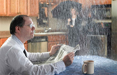 picture of a guy sitting in his kitchen with water raining in from the leaky ceiling for strongsville ohio roofing