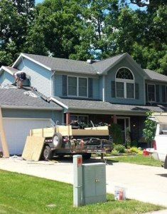 picture of a blue house showing our roofer in medina ohio putting a new roof onto a house for home improvement in medina ohio