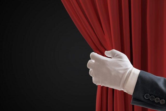 Hand zieht Vorhang auf