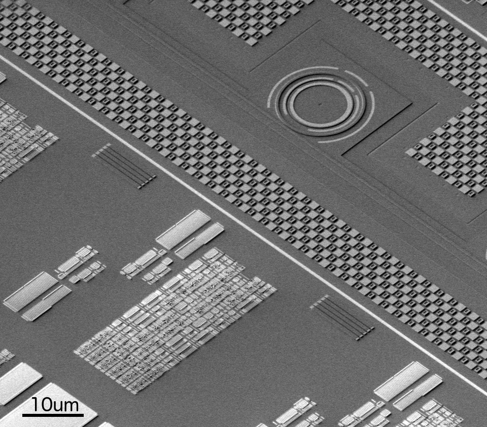 Three-dimensional electron microscope image of a region of the MIT-UC Berkeley-BU electronic photonic chip, showing a photonic ring resonator in the top right alongside an electronic circuit block in the bottom left.
